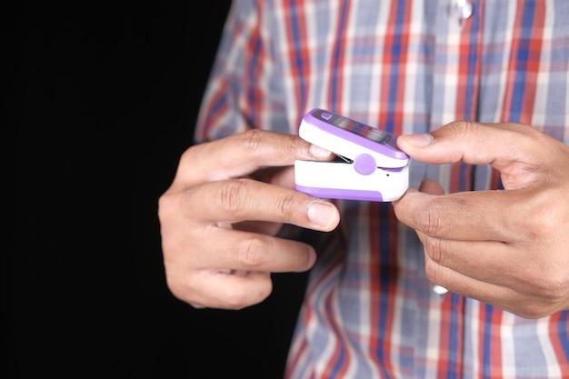 Gros plan de la main de l'homme à l'aide de l'oxymètre de pouls isolé sur fond noir