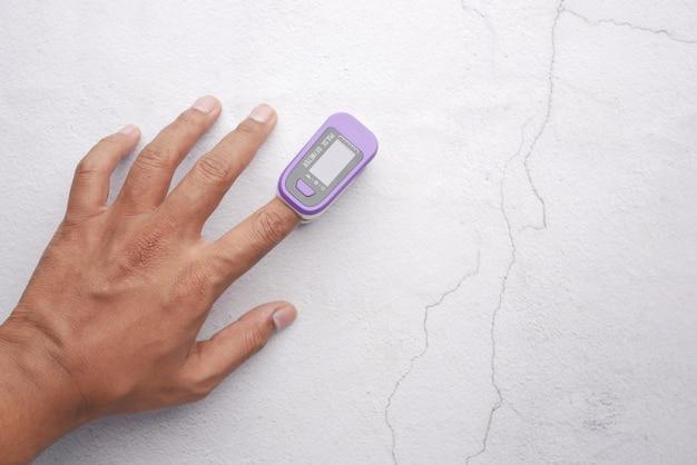 Gros plan de la main de l'homme à l'aide de l'oxymètre de pouls