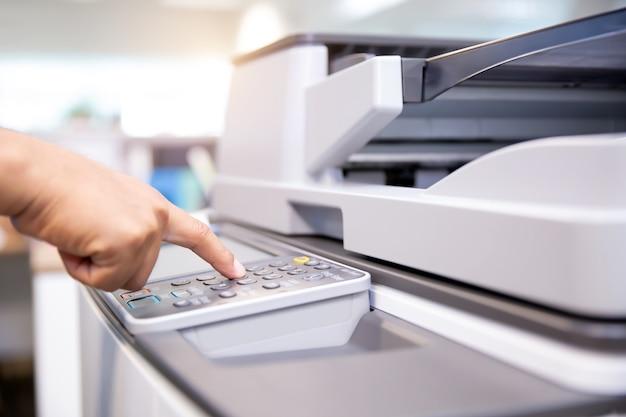 Gros plan sur la main de l'homme de bureau, appuyez sur le bouton du copieur.