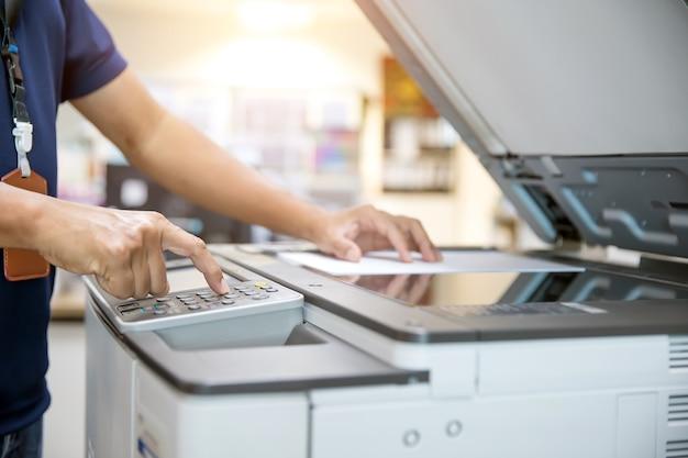 Gros plan de la main de l'homme de bureau est d'appuyer sur le bouton du panneau et de mettre du papier sur le copieur.