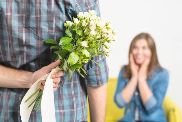 Gros plan d'une main d'homme cachant des fleurs à sa petite amie