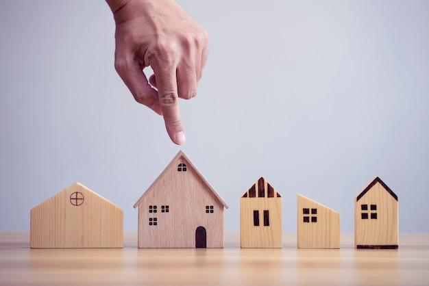 Gros plan de la main de l'homme choisissant le modèle en bois de la maison et envisageant d'acheter une propriété