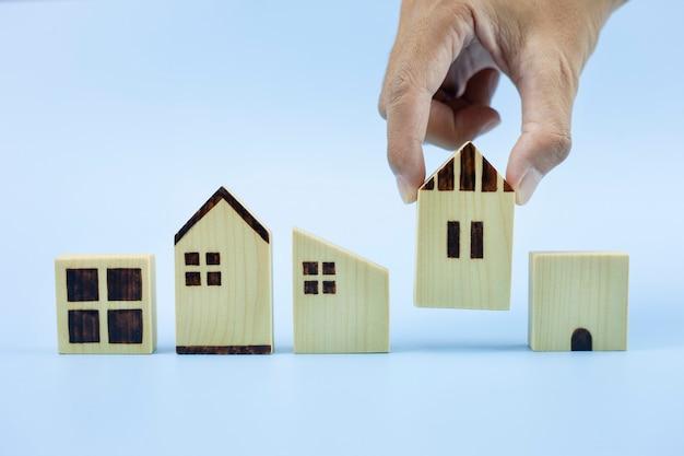 Gros plan de la main de l'homme choisissant le modèle de maison et prévoyant d'acheter le concept de prêt immobilier
