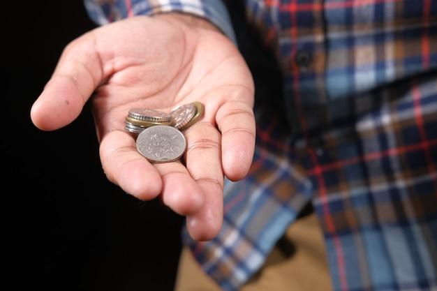 Gros plan de la main de l'homme comptant des pièces de monnaie