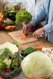 Gros plan, main homme, coupe, carotte, sur, planche découpage, à, couteau, sur, cuisine, bois, counter