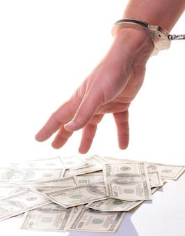 Gros plan de la main de l'homme dans des menottes métalliques fermées prêt à ramasser de l'argent en dollars américains isolé sur un mur blanc. série illégal de gains d'argent, de pots-de-vin, de corruption, de crimes et de sanctions