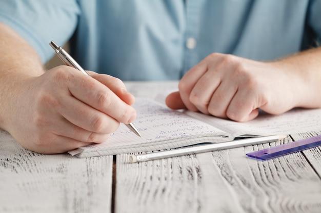 Gros plan de la main de l'homme écrit sur du papier, écrit des mathématiques en désordre, étudiant tenant un stylo à faire ses devoirs à la maison, calcule les résultats sur papier, concept d'éducation