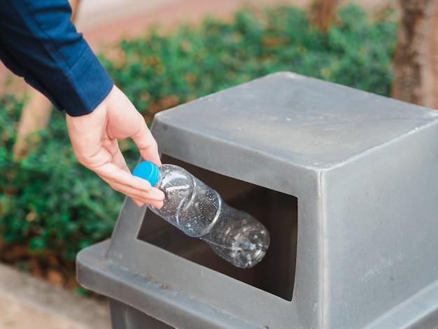 Gros plan de la main de l'homme jetant une bouteille d'eau en plastique vide dans une poubelle.