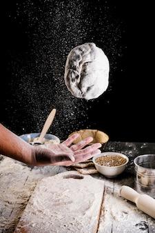 Gros plan de la main de l'homme jetant la pâte à pain en l'air