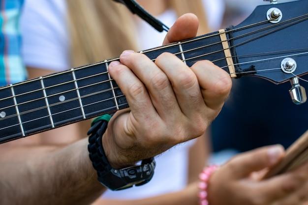 Gros plan de la main de l'homme jouant de la guitare. pratique de la guitare.