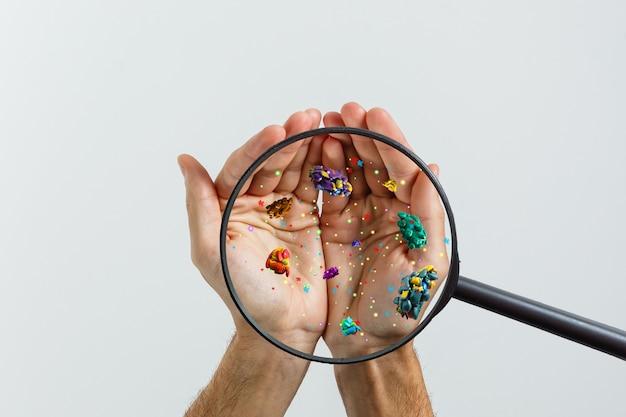 Gros plan sur la main d'un homme malade à travers une loupe transmettant le virus par contact avec la peau rendu 3d