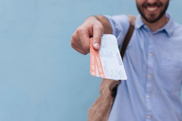 Gros plan de la main de l'homme montrant le billet d'avion sur fond bleu
