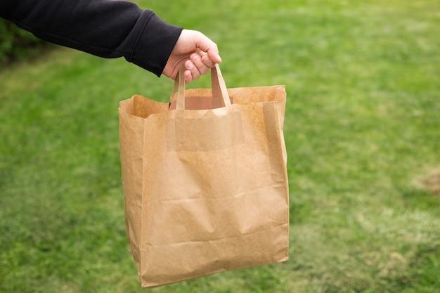 Gros plan de la main de l'homme avec un sac en papier écologique pour les plats à emporter sur fond vert nature. livraison par tous les temps 24 heures sur 24 au client.