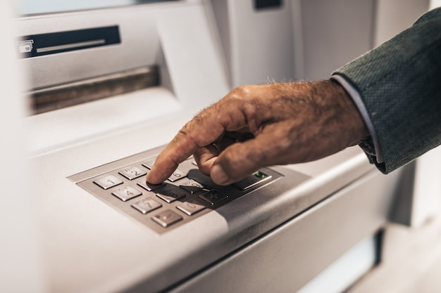Gros plan de la main de l'homme senior. il tape le code pin sur le clavier du guichet automatique.