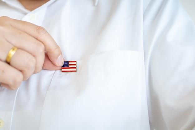 Gros plan de la main de l'homme tenant la broche de drapeau de nation des états-unis d'amérique sur le drapeau de la chemise blanche.