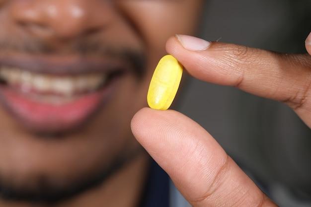 Gros plan de la main de l'homme tenant des pilules