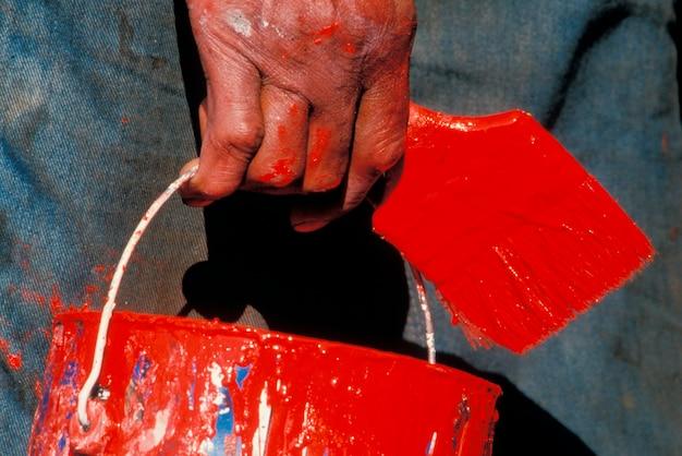 Gros plan de la main de l'homme tenant le pinceau et la boîte de conserve de peinture rouge