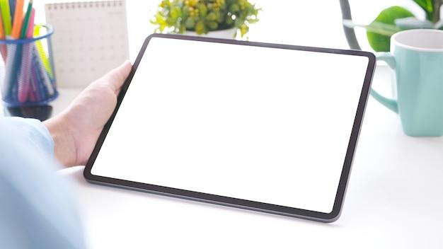 Gros plan d'une main d'homme tenant une tablette numérique avec écran noir sur fond de table de travail pour maquette, modèle