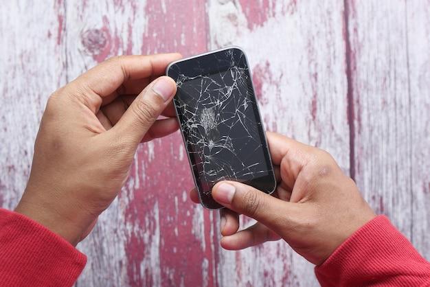 Gros plan de la main de l'homme tenant un téléphone intelligent cassé.