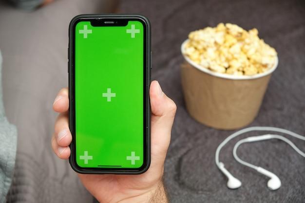 Gros plan de la main de l'homme tenant un téléphone mobile avec logo xxx