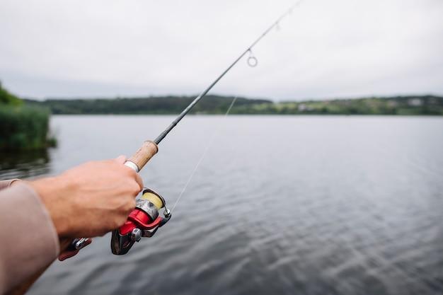 Gros plan, de, main homme, tenue, canne à pêche, sur, les, lac