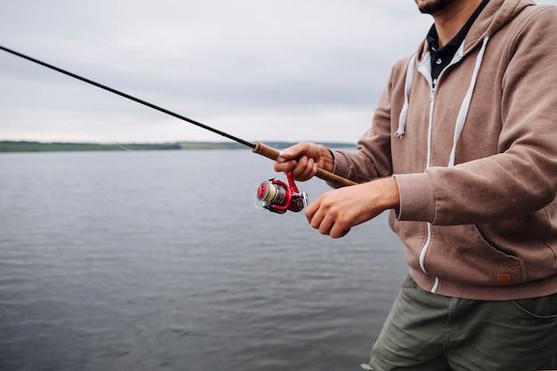 Gros plan, de, main homme, tenue, canne à pêche, près, les, lac