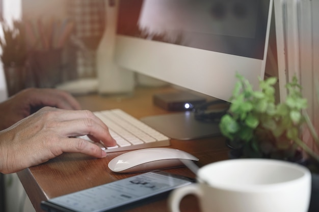 Gros plan de la main de l'homme travaillant avec l'ordinateur de bureau au bureau