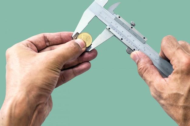 Gros plan, la main d'un homme utilise vernier pour mesurer la taille d'une pièce isolée sur fond de couleur pastel.
