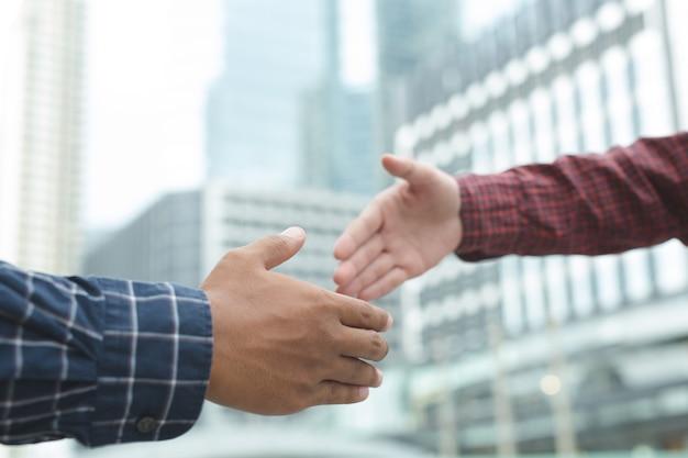 Gros plan d'une main d'hommes d'affaires serrer l'investisseur entre deux collègues ok, réussir en affaires se tenant la main.