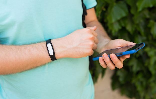 Gros plan sur la main des hommes avec un tracker d'activité et un téléphone intelligent à l'extérieur