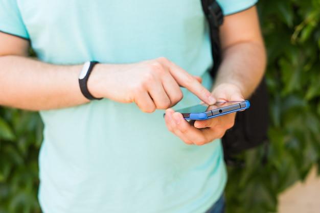 Gros plan sur la main des hommes avec un tracker de fitness et un téléphone intelligent à l'extérieur.