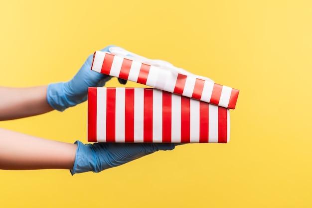 Gros plan de la main humaine dans des gants chirurgicaux bleus tenant et ouvrant une boîte cadeau blanche à rayures rouges.