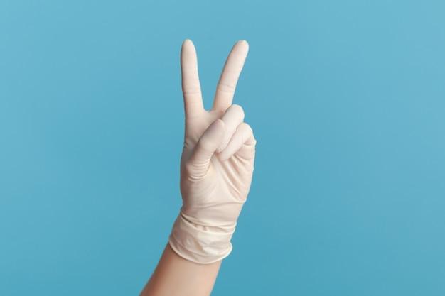 Gros plan de la main humaine dans des gants chirurgicaux montrant la victoire, le signe de paix ou le numéro 2 avec les doigts.