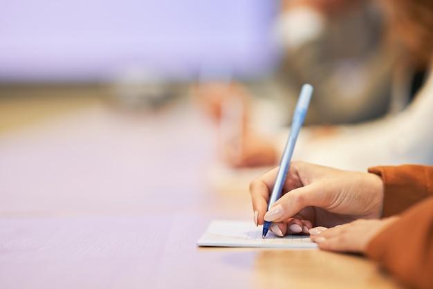 Gros plan sur une main humaine écrivant quelque chose sur le papier au premier plan