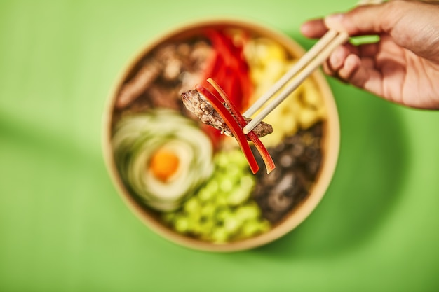 Gros plan d'une main humaine tenant un morceau de viande avec du poivron rouge par des bâtons chinois