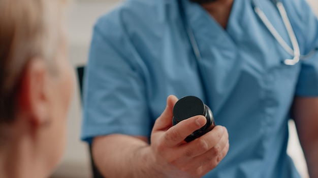 Gros plan d'une main d'infirmière tenant une bouteille de pilules et de capsules