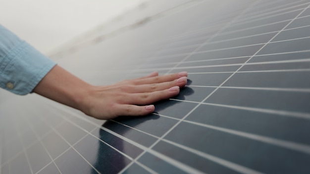 Gros plan sur une main d'ingénieur femme vérifie avec des panneaux solaires. la main du travailleur et le panneau solaire pendant le coucher du soleil. concept pour l'écologie. ferme solaire. concept d'énergie propre.