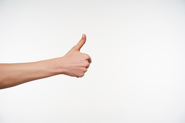 Gros plan sur la main de la jeune femme avec manucure blanche pouce vers le haut