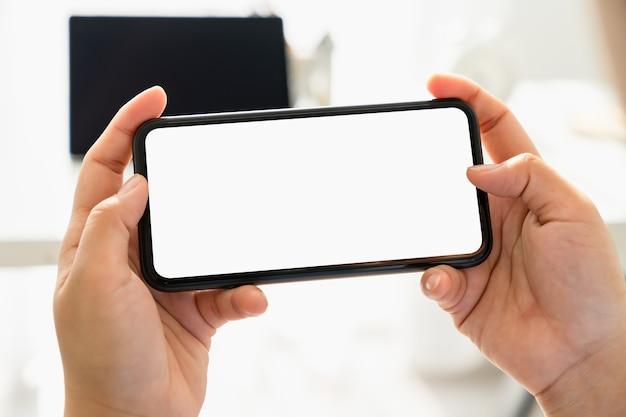 Gros plan de la main de la jeune femme tenant le smartphone sur la table et l'écran est vide, concept de réseau social.