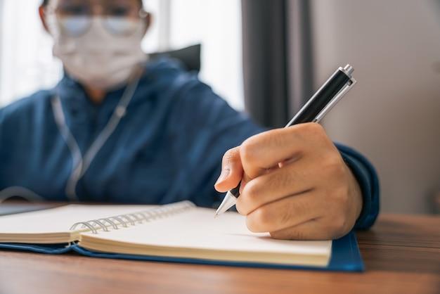 Gros plan sur la main d'une jeune fille portant un masque écrivant une note sur un livre à la recherche d'un ordinateur portable de vidéoconférence en ligne sur internet apprentissage à distance à la maison
