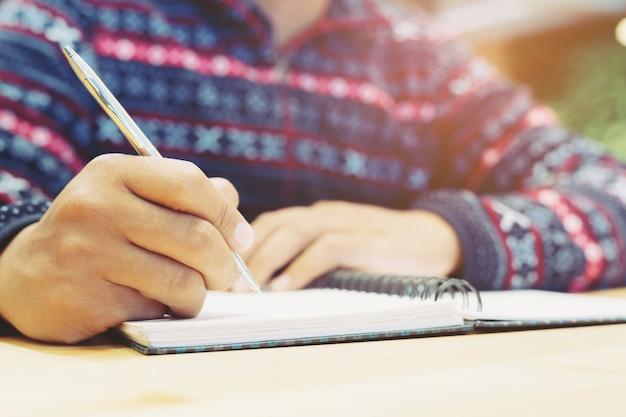 Gros plan main jeune homme sont assis à l'aide d'un stylo écrivant le bloc-notes de conférence dans le livre sur le bois de la table