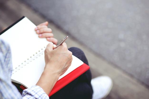 Gros plan main jeune homme utilise un stylo écrit bloc-notes de conférence dans le livre assis sur la chaise en plein air.