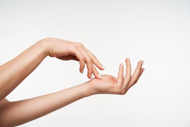 Gros plan sur la main levée de la jeune femme séduisante touchant doucement avec les doigts