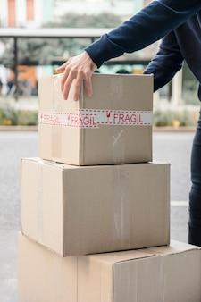 Gros plan de la main d'un livreur ramasser une boîte en carton