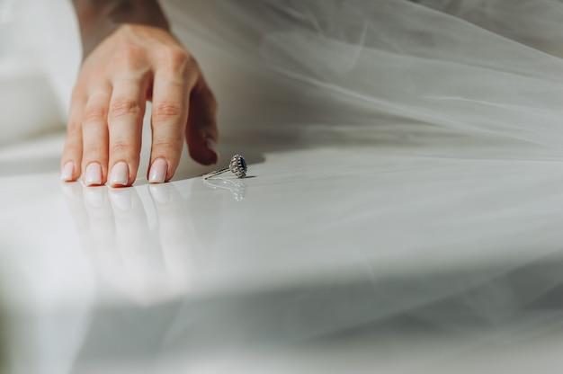 Gros plan de la main de la mariée avec une belle manucure douce et une bague vintage avec un diamant bleu sur le rebord de la fenêtre. matin de la mariée.