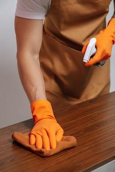 Gros plan sur la main masculine à l'aide de lingettes en tissu sur l'armoire en bois avec tiroir et tenant le flacon pulvérisateur pour nettoyer les meubles à la maison