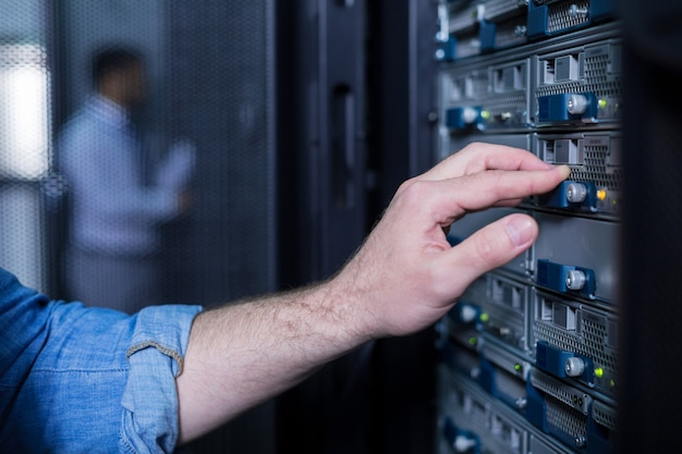Gros plan d'une main masculine en appuyant sur le bouton tout en travaillant avec le système de données de stockage dans la salle des serveurs