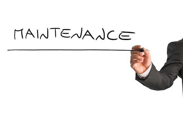 Gros plan d'une main masculine écrivant le mot maintenance sur un écran virtuel blanc.