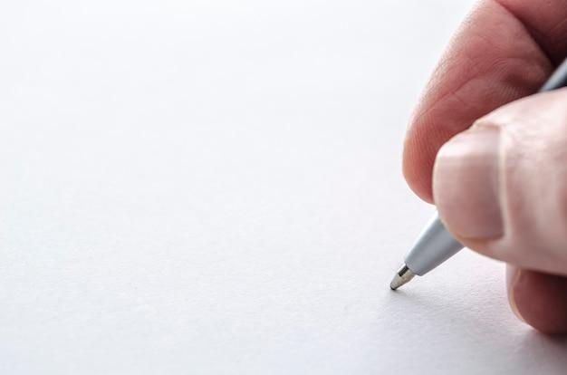 Gros plan d'une main masculine écrivant sur un papier vierge.