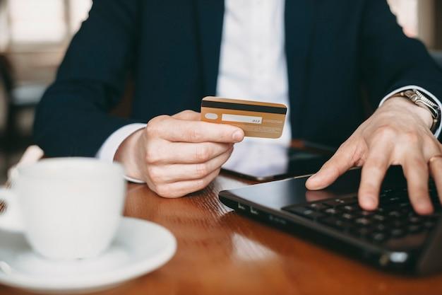 Gros plan d'une main masculine habillée en costume tenant une carte de crédit d'or alors qu'il était assis sur une table avec un ordinateur portable.